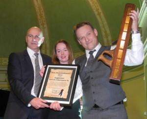 En stolt Lars-Erik Zakariassen hever trofeet han er overrakt av Raymond Myrland og Monica Blom Thorsen